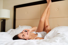 Woman lying upside down in bed talking on cell phone. Royalty Free Stock Image