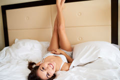 Woman lying upside down with legs against headboard. Stock Images