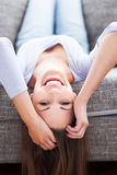 Woman lying upside down on sofa Stock Image