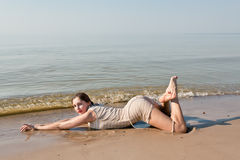 Woman lying in water on beach Stock Photography