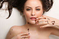 Woman lying on white. Attractive young woman lying on white background with chocolate smeared Royalty Free Stock Photos