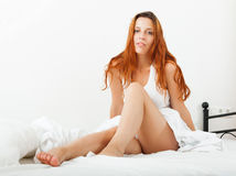 Woman lying on white sheets on the bed at home Stock Image