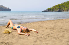 Woman is lying on the wild beach Stock Photos