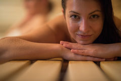 Woman lying on wooden bench at sauna