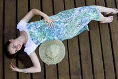 Woman lying on wooden deck. Serene woman resting on wooden deck stock photo