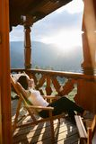 Woman is lying on wooden deck chair and relaxes looking at beautiful mountain resort scenic on sunset. Young slim female Stock Image