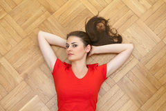 Woman lying on the wooden floor Royalty Free Stock Image
