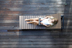 Woman lying on wooden sunbed. Young woman lying on wooden sunbed Stock Image