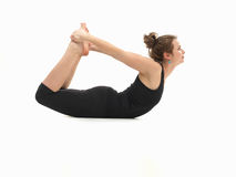Woman in lying yoga posture. Young attractive woman on the floor, in reversed yoga pose, side view, dressed in black on white background Royalty Free Stock Photos