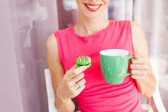 Woman with macaroon. Beautiful woman enjoying a cup of tea and macaroon. Lovely color combination of pink and green Royalty Free Stock Photography
