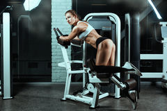 Woman on the machine for bodybuilders doing exercise. Royalty Free Stock Photo