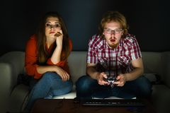 Woman is bored while man playing games Royalty Free Stock Image