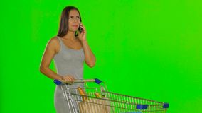 Woman made the purchase and calls on mobile. Green screen stock video