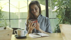 Woman made successful payment with credit card and mobite phone. Caucasian model with long brown hair. Cup of matcha and notebook on the table stock video