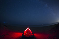 Woman maditating in a tent in the night with sky full of stars Royalty Free Stock Photo