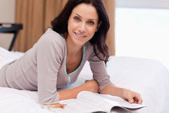 Woman with magazine lying on the bed Royalty Free Stock Photography