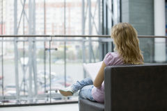 Woman With Magazine Sitting On Sofa In Shopping Mall. Rear view of young women with magazine sitting on sofa in shopping mall Royalty Free Stock Photo