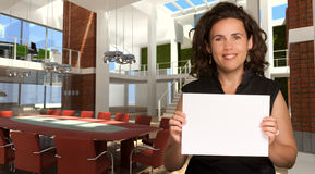 Woman in magnificent office holding a blank sign Stock Photos