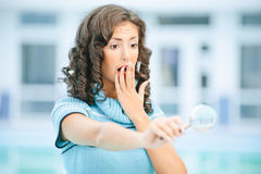 Woman with magnifier. Amazed young dark-haired woman in blue sweater looks at object of research through magnifier Stock Photography