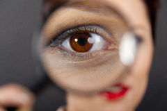 Woman with magnifier Stock Image