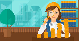Woman with magnifier and golden coins. A woman holding a magnifier and looking at stacks of golden coins on the background of panoramic modern office with city Royalty Free Stock Photo