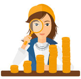 Woman with magnifier and golden coins Stock Photos