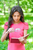 Woman with magnifier holds book Stock Photo