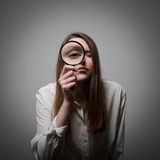 Woman with magnifier Stock Images