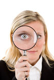 Woman with magnifying glass. A woman with a magnifying glass over her eye royalty free stock photo