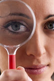 Woman with magnifying glass. Woman looking through a magnifying glass Royalty Free Stock Photo