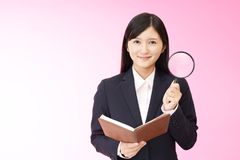 Woman with a magnifying glass. Business woman who checks the schedule Royalty Free Stock Photo
