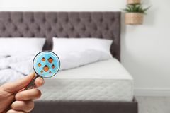 Woman with magnifying glass detecting bed bugs on mattress, closeup. Space for text stock photos
