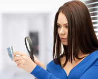 Woman with magnifying glass and euro cash money royalty free stock images