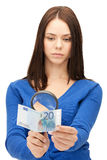 Woman with magnifying glass and euro cash money Stock Photo