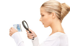Woman with magnifying glass and euro cash money Stock Photos