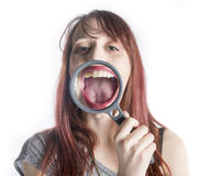 Woman with Magnifying Glass in front of Open Mouth Royalty Free Stock Image