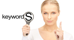 Woman with magnifying glass and keywords word Royalty Free Stock Photo