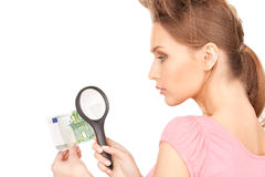 Woman with magnifying glass and money Royalty Free Stock Image