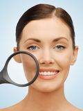 Woman with magnifying glass over acne Stock Photo