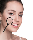 Woman with magnifying glass showing aging skin Stock Photo