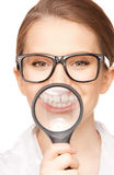 Woman with magnifying glass showing teeth Royalty Free Stock Photography