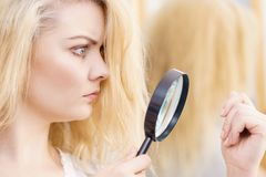 Woman magnifying her split ends hair royalty free stock images