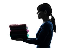 Woman maid housework holding sweater pile silhouette Royalty Free Stock Images