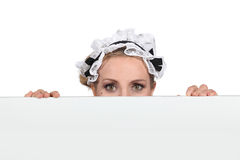 Woman in maid outfit. Hiding behind message board stock photo