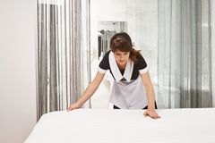 Woman in maid uniform making bed. Portrait of female housecleaner putting on new blankets and clean hotel room, trying. Her best not to miss any spot and let stock image