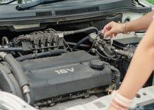 Woman& x27 ; main de s vérifiant le moteur de voiture avant le voyage photos libres de droits