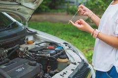 Woman& x27 ; main de s vérifiant le niveau d'huile à moteur d'automobiles sur le dipsti photographie stock