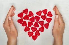 Woman& x27 ; mains de s avec le coeur fait à partir des bonbons à gelée Photos libres de droits