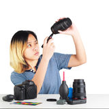 Woman maintenance a DSLR Camera with lens brush Stock Photo