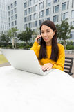 Woman make a call by cellphone and use of the notebook computer Stock Photos